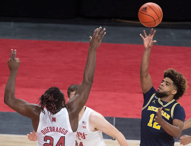 Mike Smith from Michigan (12) shoots Evan Widraogo from Nebraska (24) during an NCAA College basketball match in Lincoln, NEP, Friday, December 25, 2020.