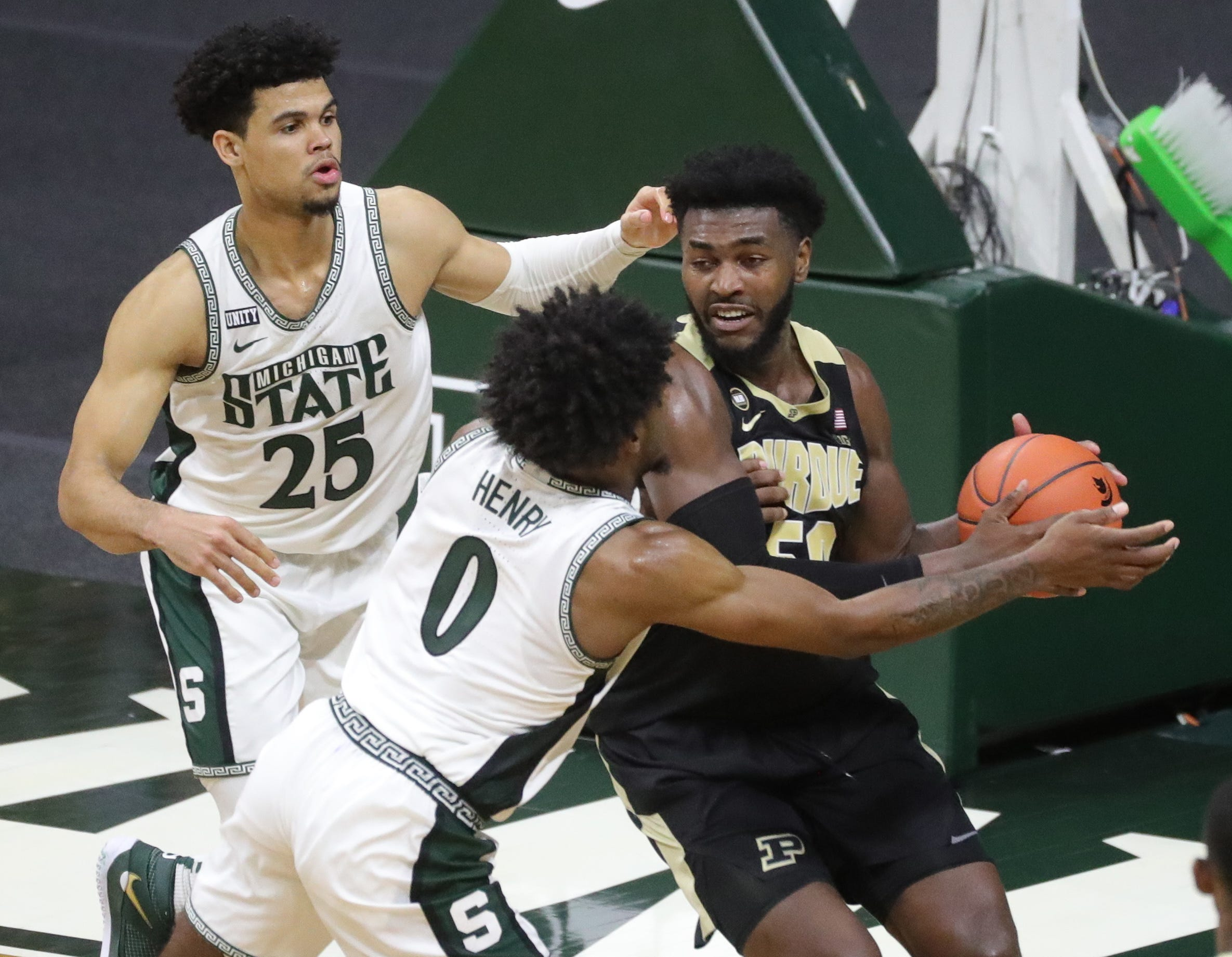 Michigan State Spartans striker Malik Hall (25) and Aaron Henry defend Purdue Boilermakers striker Trevion Williams during the second half at Priceline Center in East Lansing, Friday, Jan.8, 2021.