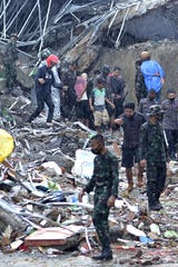 Rescue workers lead residents to safety in Mamuju on January 15, 2021, after a magnitude 6.2 earthquake hit the Indonesian island of Sulawesi.