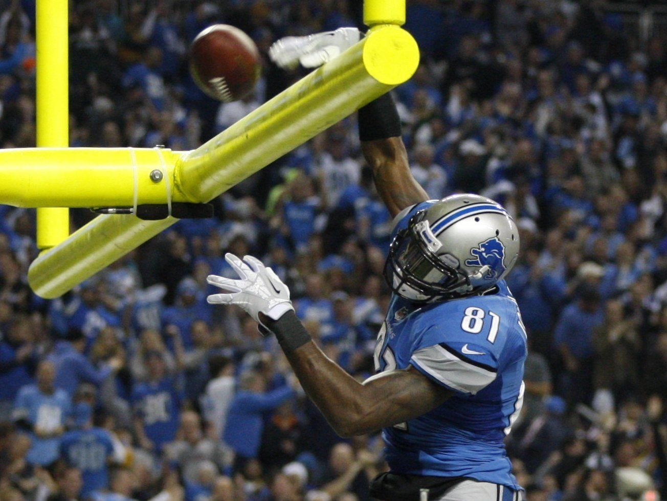 Calvin Johnson dips the ball over the goal post after landing in the third quarter against the Green Bay Packers in Detroit on November 28, 2013.